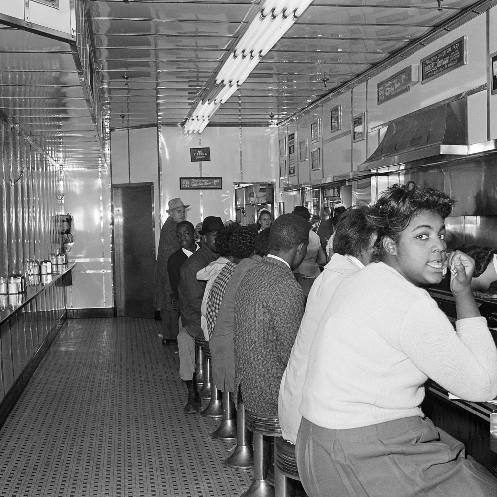 "PAGE 61: IN EXAMINING AFRICAN-AMERICANS' QUEST FOR FREEDOM, NONVIOLENT DIRECT-ACTION TACTICS VARIED BASED ON, IN THE WORDS OF CONGRESSMAN JOHN LEWIS, ""DIFFERENT FORMS OF OPPRESSION."" PICTURED HERE, ATLANTA UNIVERSITY CENTER STUDENTS STAGE A SIT-IN AT A DOWNTOWN ATLANTA LUNCH COUNTER IN JANUARY 1964 (PERMISSION OF THE ASSOCIATED PRESS)."
