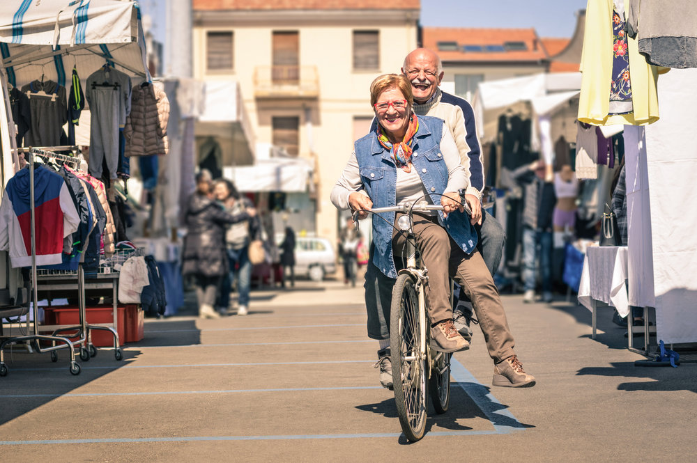 stock-photo-happy-senior-couple-having-fun-with-bicycle-at-flea-market-concept-of-active-playful-elderly-with-274716779.jpg