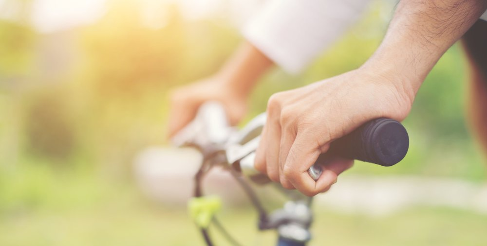 Close Up on biking man hands on the blurred nature sunrise backg