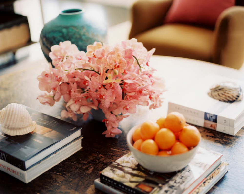 We are always looking at interior design resources for new ideas and color combination. Here an arrangement of delicate pink orchids work so nicely with the teal vase and bowl of orange clementines. Pulled from our  Pinterest  page.