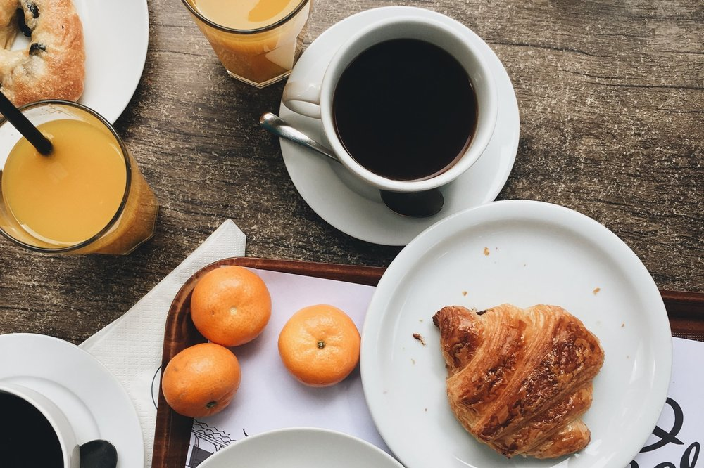 A photograph of coffee, croissants and orange juice.