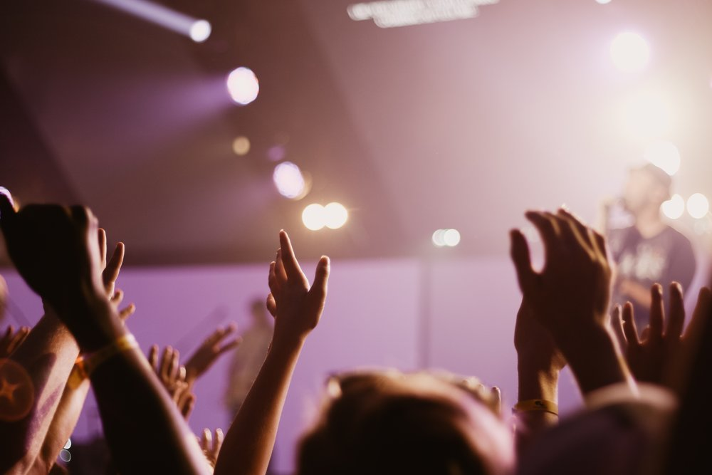 A photograph of hands raised in worship