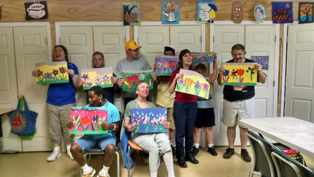 Participants at Sunnyhill University showing off their artwork