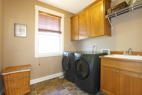 A pantry room with beige walls and a dishwasher, sink, hamper, and window.