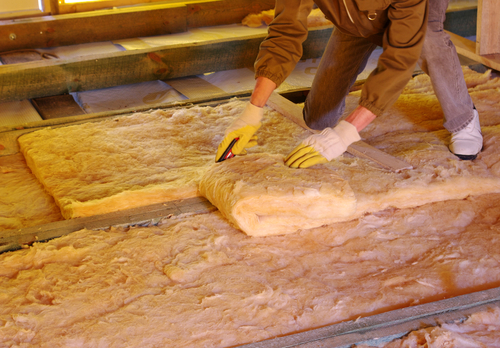A construction worker installing new insulation into an attic.