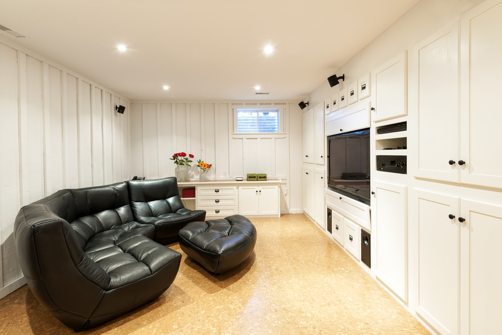 Finished basement with black leather furniture.