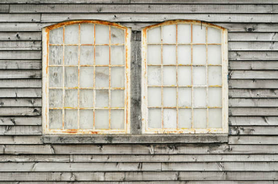 A pair of old, white window frames afflicted with rust.