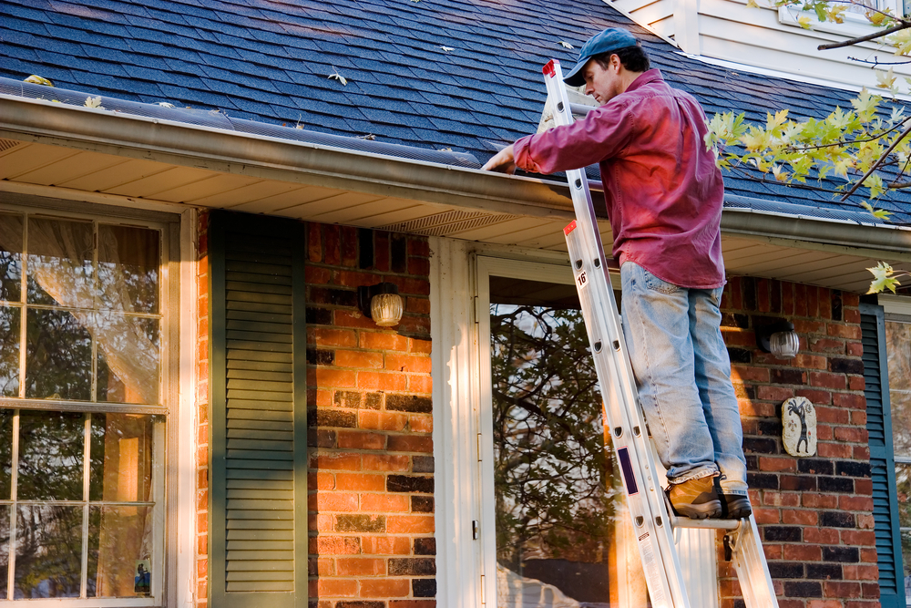 Man cleaning gutters on a home