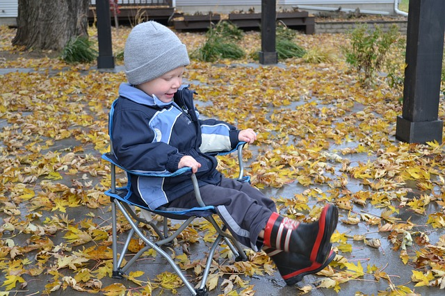 Young child sitting in backyard surrounded by fall leaves