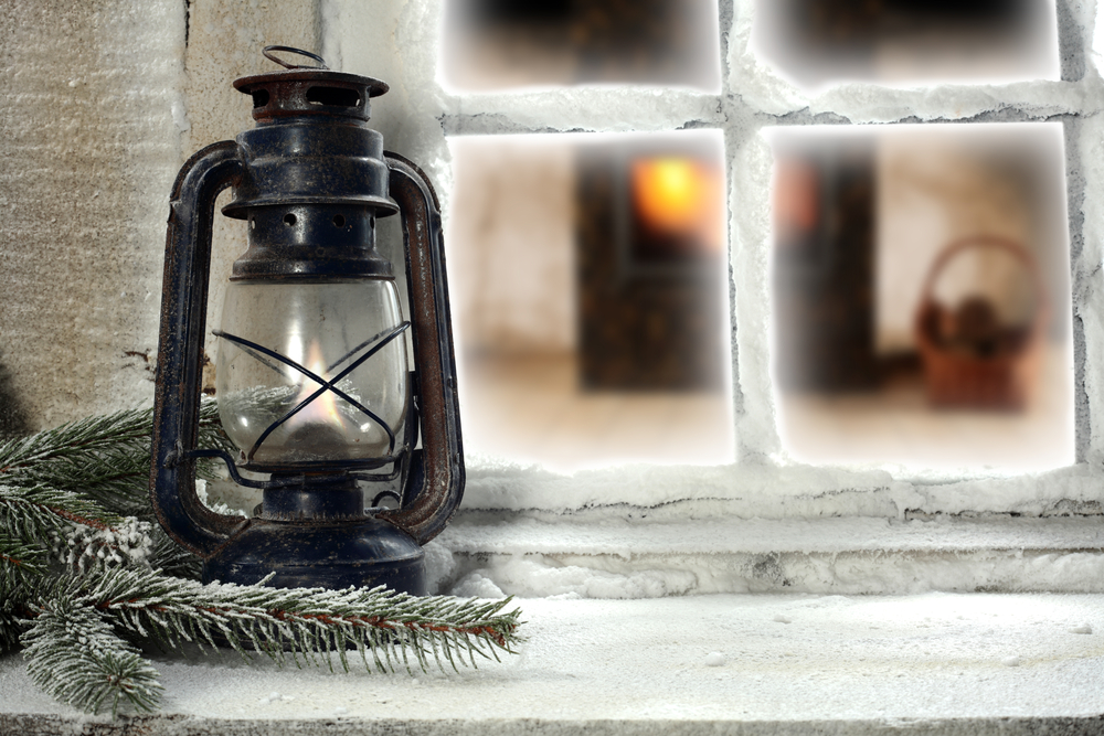 Home window in winter time decorated with a lantern and pine needles