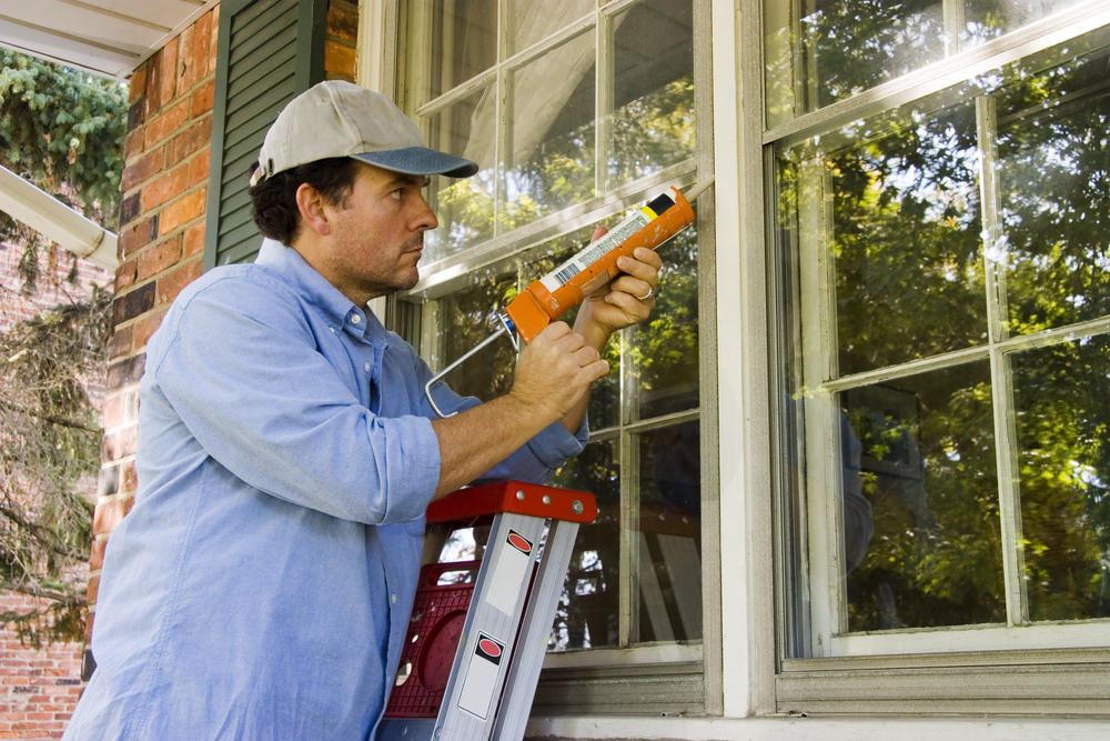 Man fixing air leak with caulk gun