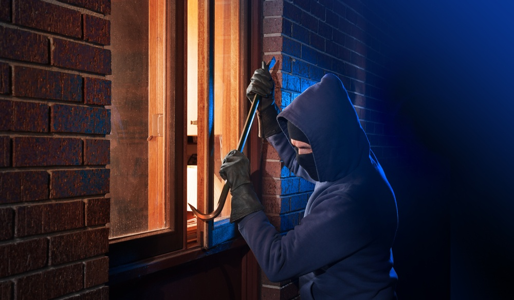 Burglar opening window to home