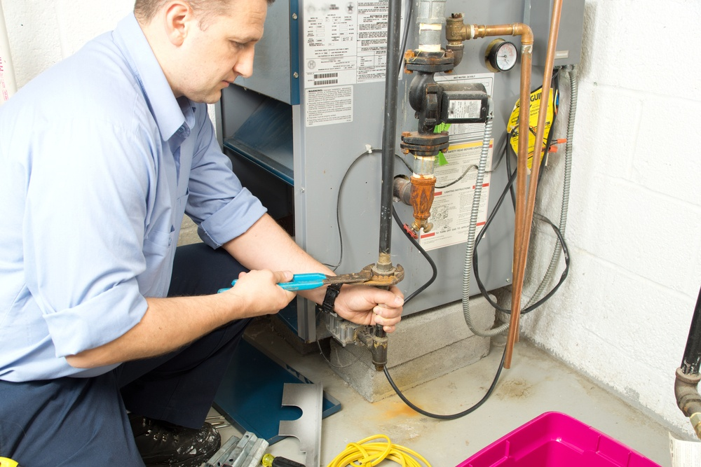 Furnace repairman repairing home furnace
