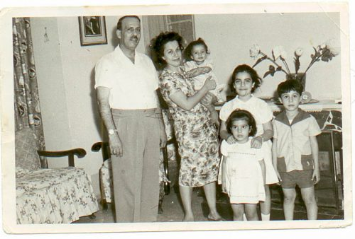 Cynthia as a baby in her mother's arms, her father and three siblings in their home in Baghdad