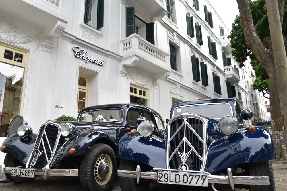 a couple of old Citroens outside Sofitel Legend Hotel