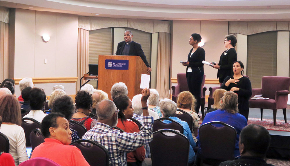 Father Bryan Massingale converses with the audience during a question-and-answer-session following his Wed, Sept. 20 talk. Biftu Bussa '18 (center on stage) and Donna Hauer, director of Multicultural and International Programs at St. Kates, moderated the Q & A. Photo by Pauline Oo.