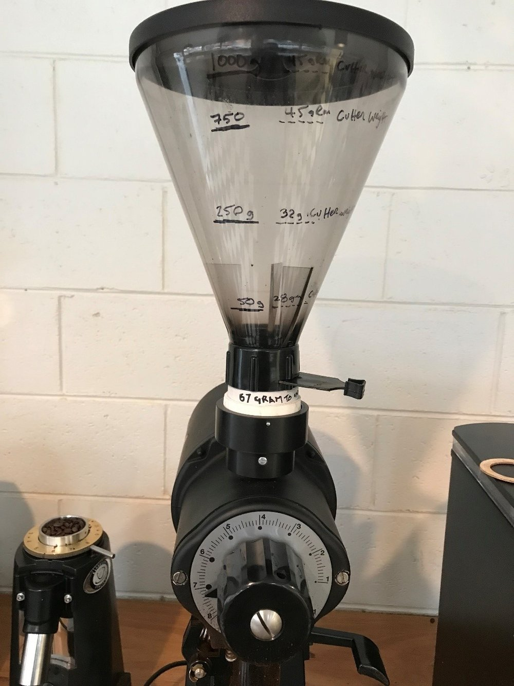 """Figure 7.    The Bush and Bush, Test rig. Markings are placed on the grinder hopper of a """"Gino Rossi conical hopper"""" to indicate when the hopper empties. This then tells us when we must top up beans so as not to change the weight on the Burrs and therefore a difference in grinding. We use this hopper on all of our grinders when testing burrs. And we make sure that the bean level is between 1000gram and 750gram lines at all times. In this way we can have confidence that bean/burr weight is not affecting the particle size and distribution of the resultant ground coffee."""