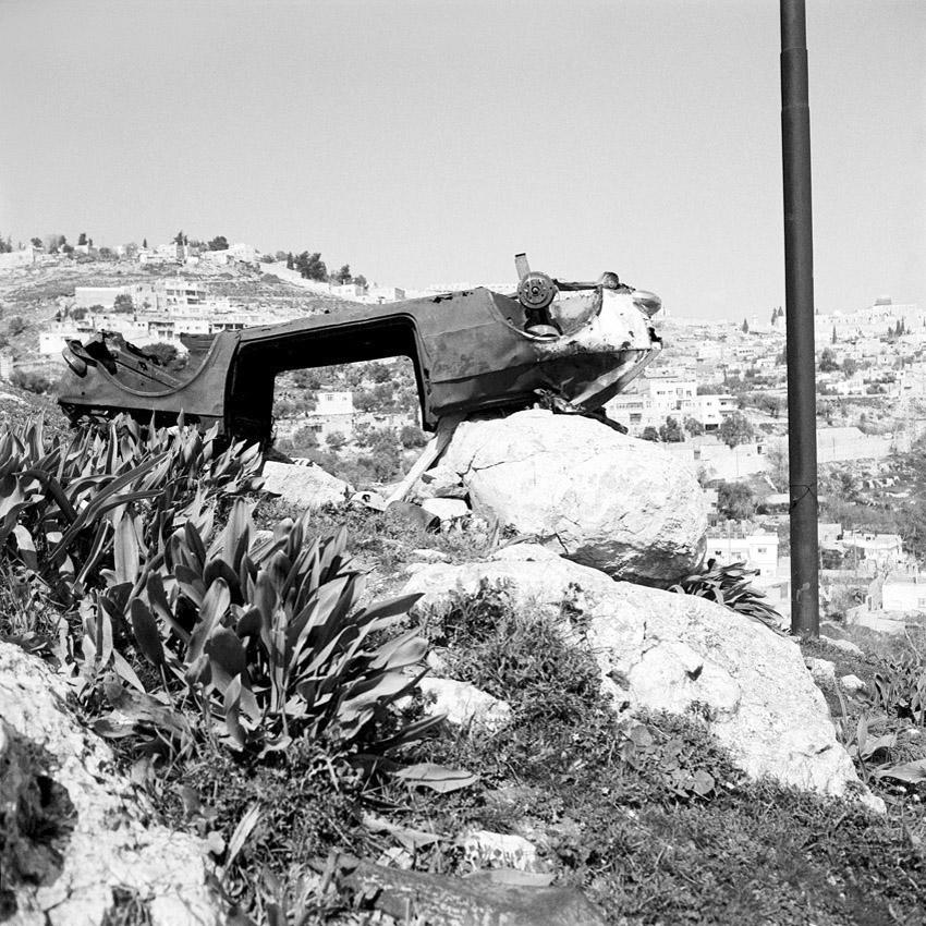 Carcasse de voiture sous les remparts de la vieille ville de Jerusalem. Le poteau fait partie de l'erouv de Jerusalem, délimitation symbolique de la communauté juive.