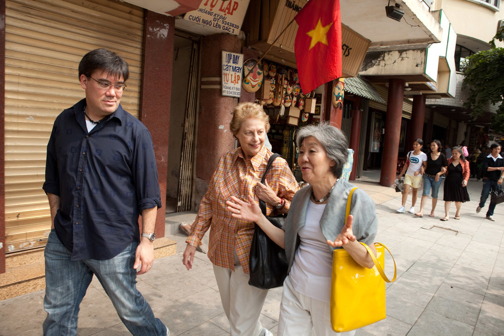 "Cultural exchange can be more than music, and while in Hanoi Alan Gilbert and his mother, Yoko Takebe (right), then a Philharmonic violinist, joined food critic Mimi Sheraton in her search for ""the perfect pho"" — the popular Vietnamese noodle soup — for an article she was writing. As Mimi Sheraton told  Smithsonian  magazine, Alan Gilbert was ""great fun, very adventurous, extremely good-natured,"" and her favorite moment was ""when our New York Philharmonic played the Vietnamese national anthem followed by 'The Star-Spangled Banner.' … I mean, chills up and down the spine."""