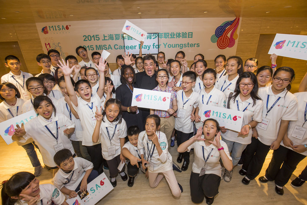 """Now a crazy pose,"" suggested Alan Gilbert as he congratulated the Very Young Composers whose works the Philharmonic performed during the Orchestra's first annual performance residency of the Shanghai Orchestra Academy and Residency Partnership: middle-schoolers Hawa Sakho of New York City (left) and Liao Shuwen of Shanghai, plus the many other kids who helped out at the Young People's Concert as ushers and journalists."