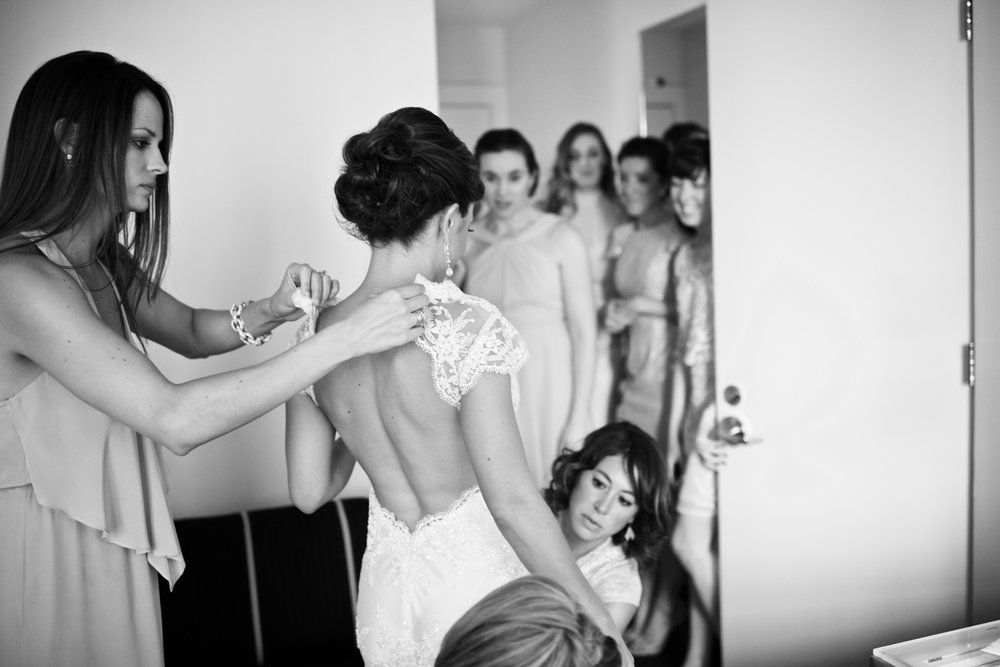 Bridesmaids help bride dress for wedding at Morgan Manufacturing in Chicago, Illinois.