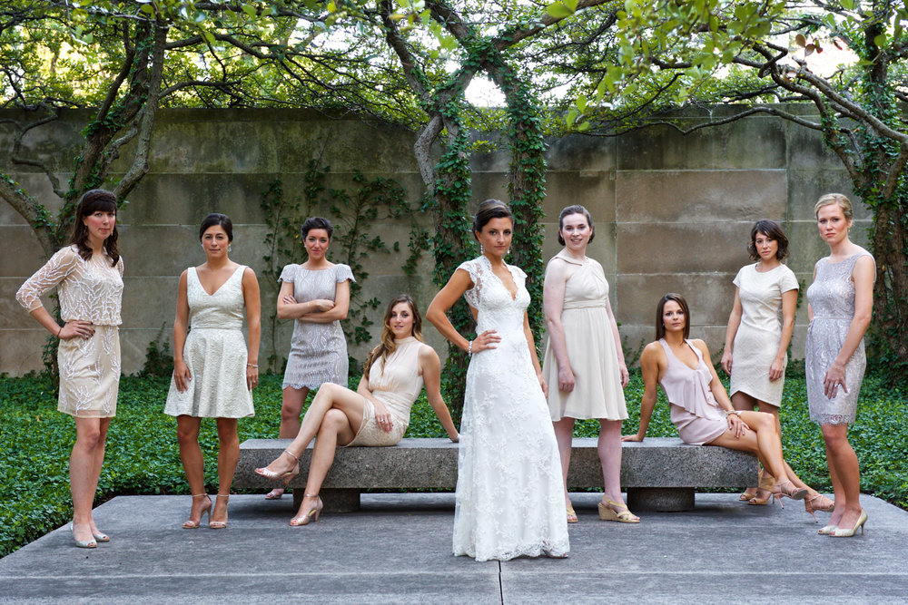 Bridesmaids wearing neutral cocktail dresses posing with the bride at the Art Institute of Chicago gardens