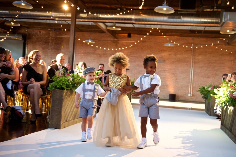 Flower girl and ring bearers walk down the aisle during wedding ceremony at Morgan Manufacturing in Chicago.