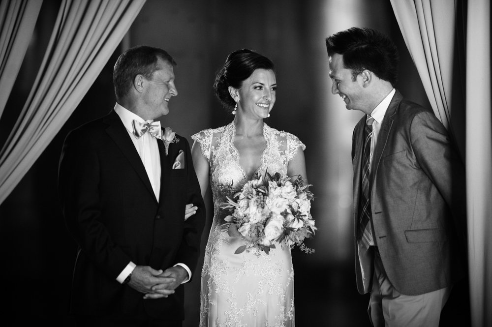 Jesse Deckard, of Bliss Weddings and Events, sends bride and her father down the aisle for her wedding ceremony at Morgan Manufacturing.