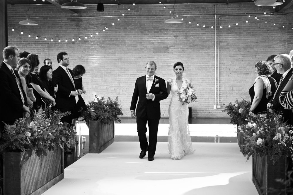 The bride and her father walk down the aisle at her Morgan Manufacturing wedding ceremony.