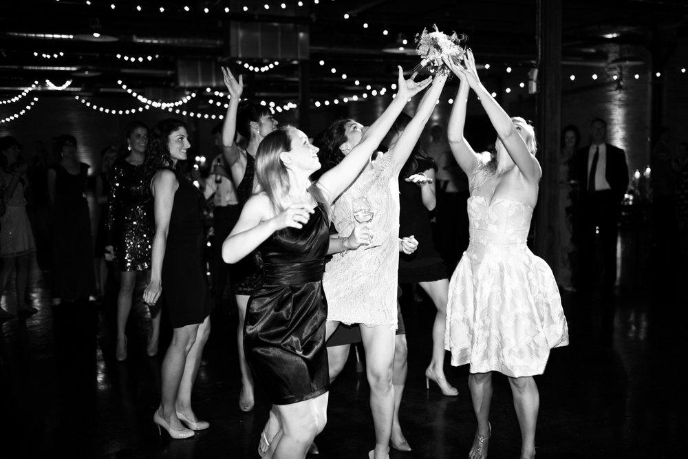 Bridesmaids catch bouquet at Morgan Manufacturing Chicago wedding.
