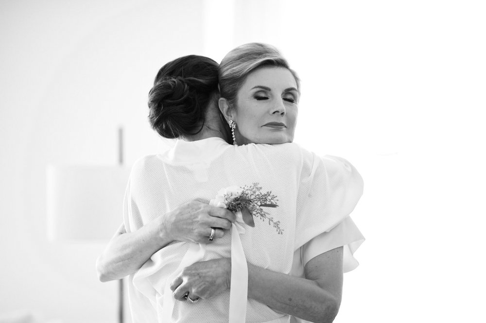 Bride and mother hug while getting ready for wedding in downtown Chicago.