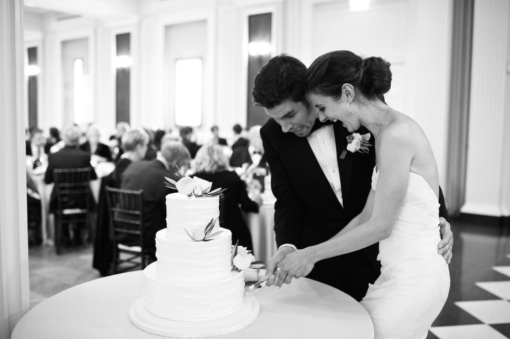 Bride and groom cut the cake at their romantic summer wedding reception at the Chicago History Museum