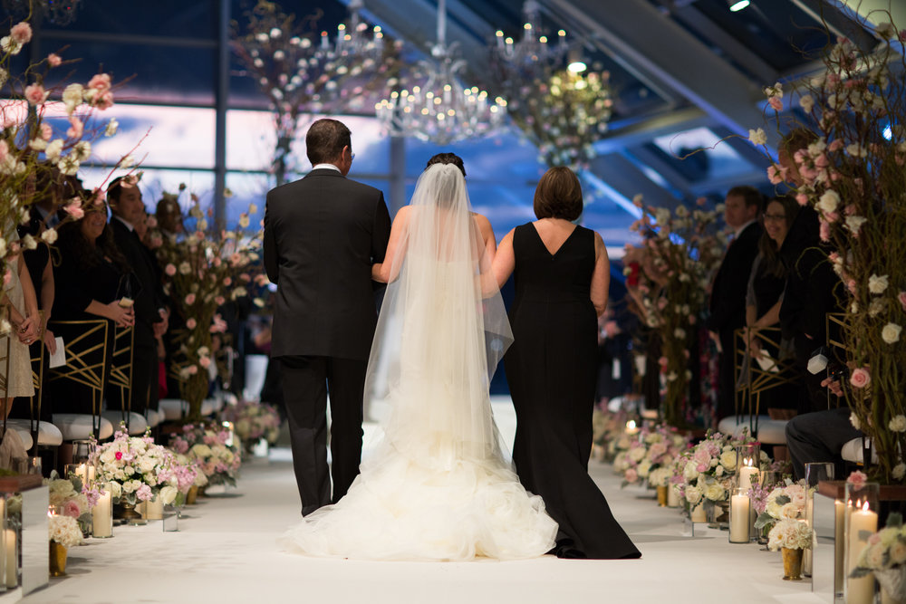 Bride and her parents walk down the aisle at Adler Planetarium wedding in Chicago