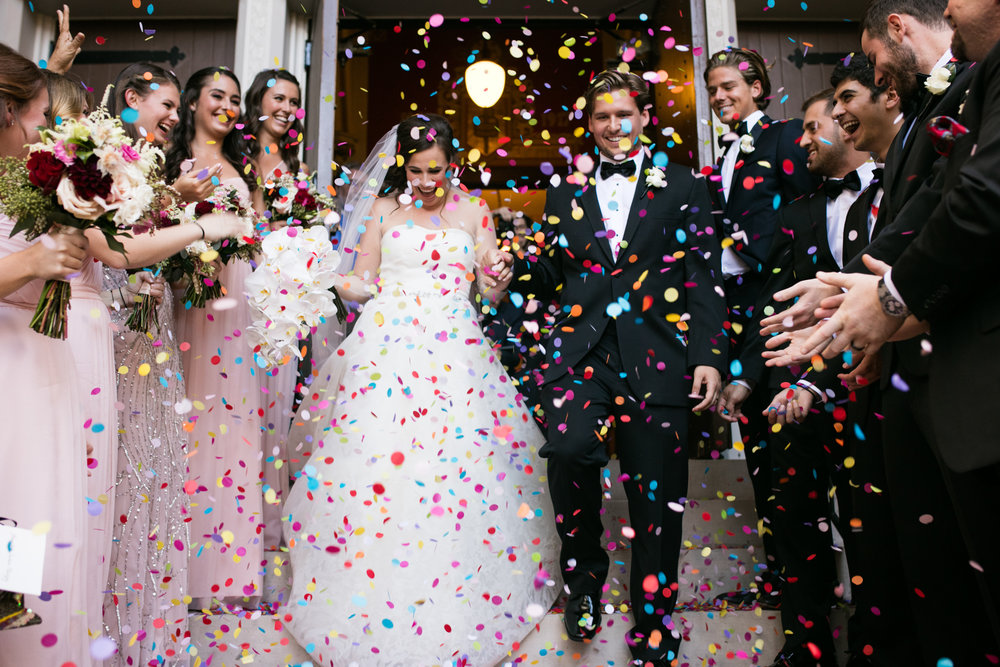 Guests throw confetti as bride and groom exit wedding ceremony at St James Lutheran Church in Chicago, Illinois