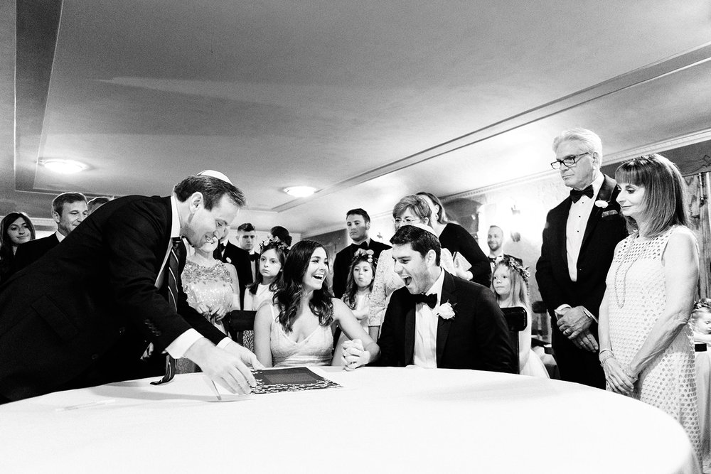 Bride and groom and their families gather to sign ketubah during their wedding at Riverbend Club in Kohler, Wisconsin near Sheboygan