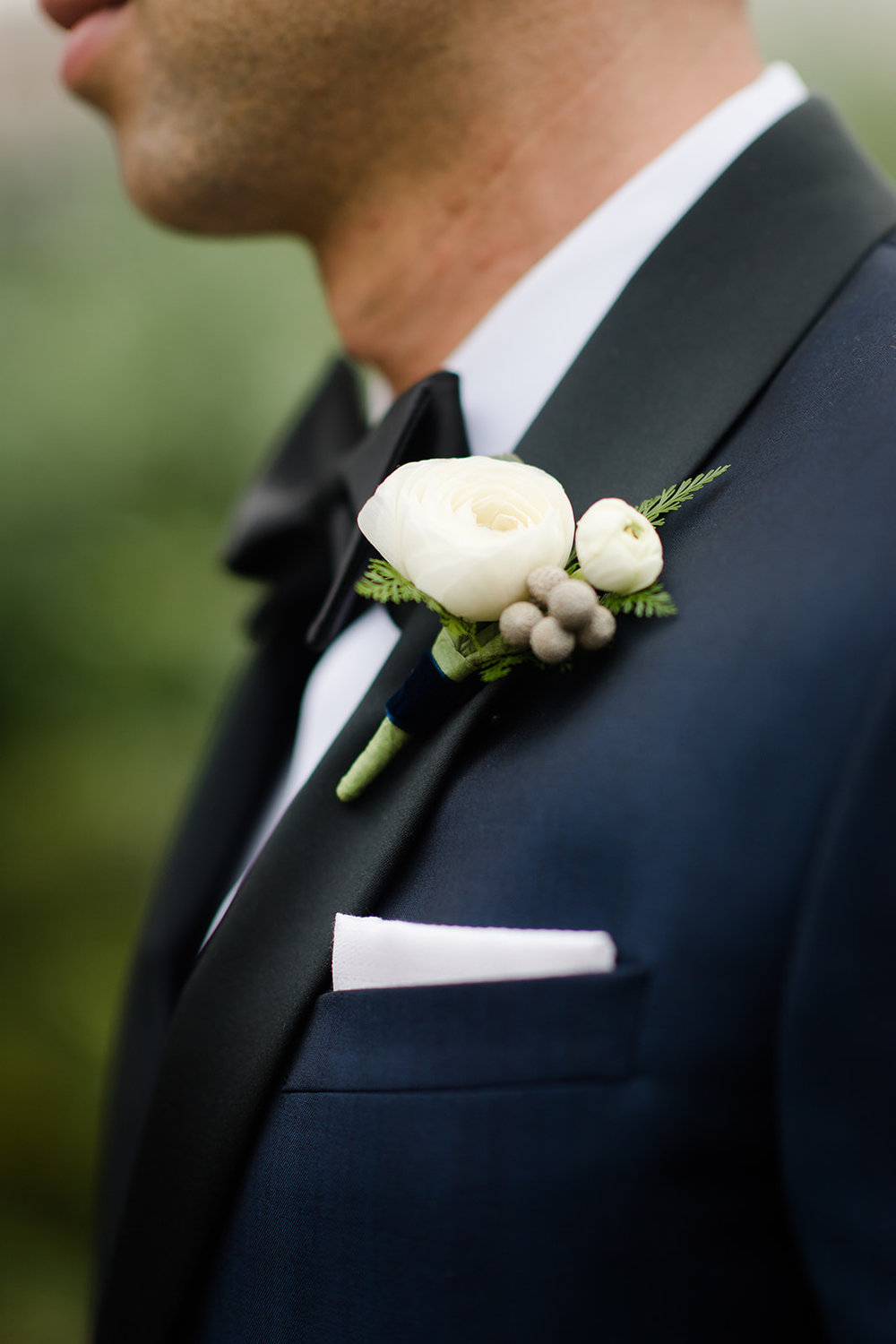 Groom in a navy and black tux with ranunculus boutonnière at Chicago black tie wedding.