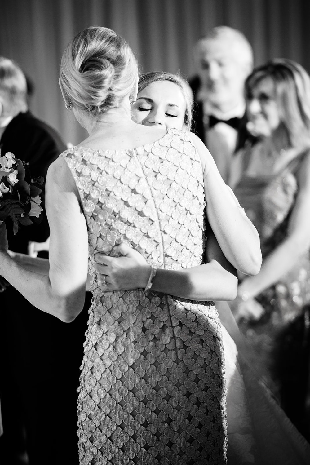 A bride hugs her mother at the beginning of the wedding ceremony in this black and white documentary wedding photo