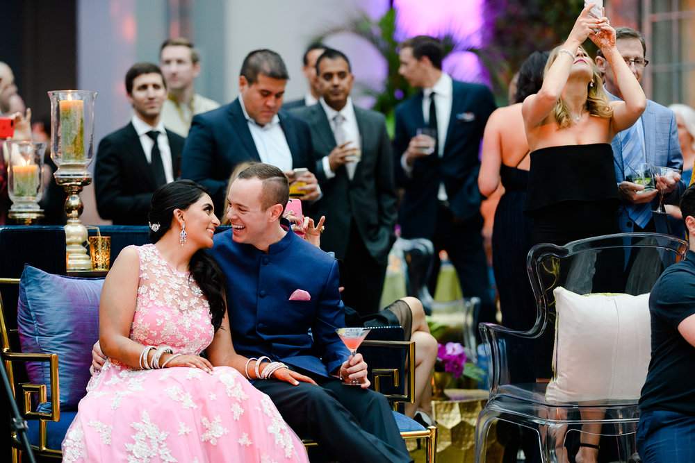 Bride and groom react to the entertainment at their sangeet in the Harold Washington Library in Chicago