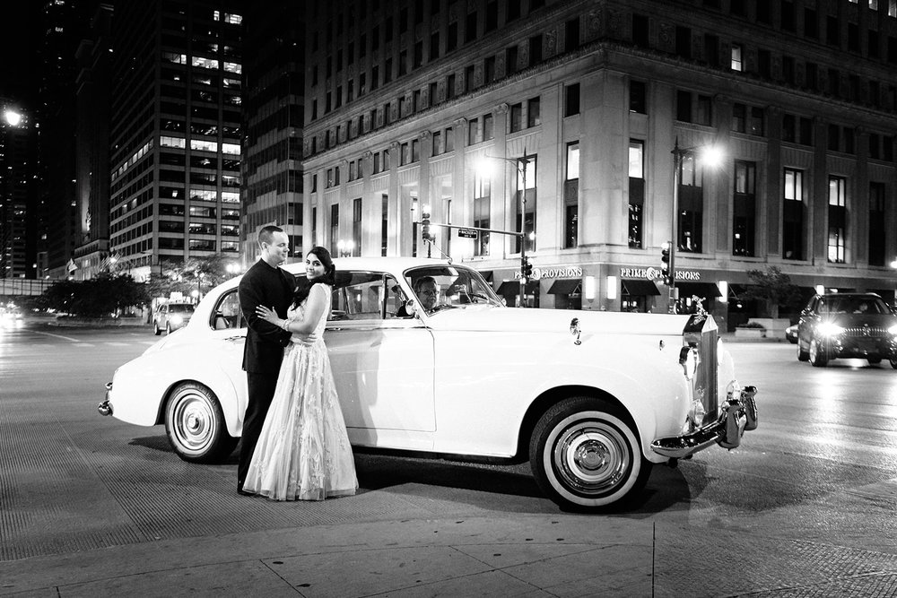 Bride and groom pose with a vintage rolls royce in downtown Chicago after their Sangeet at the Harold Washington Library Winter Garden