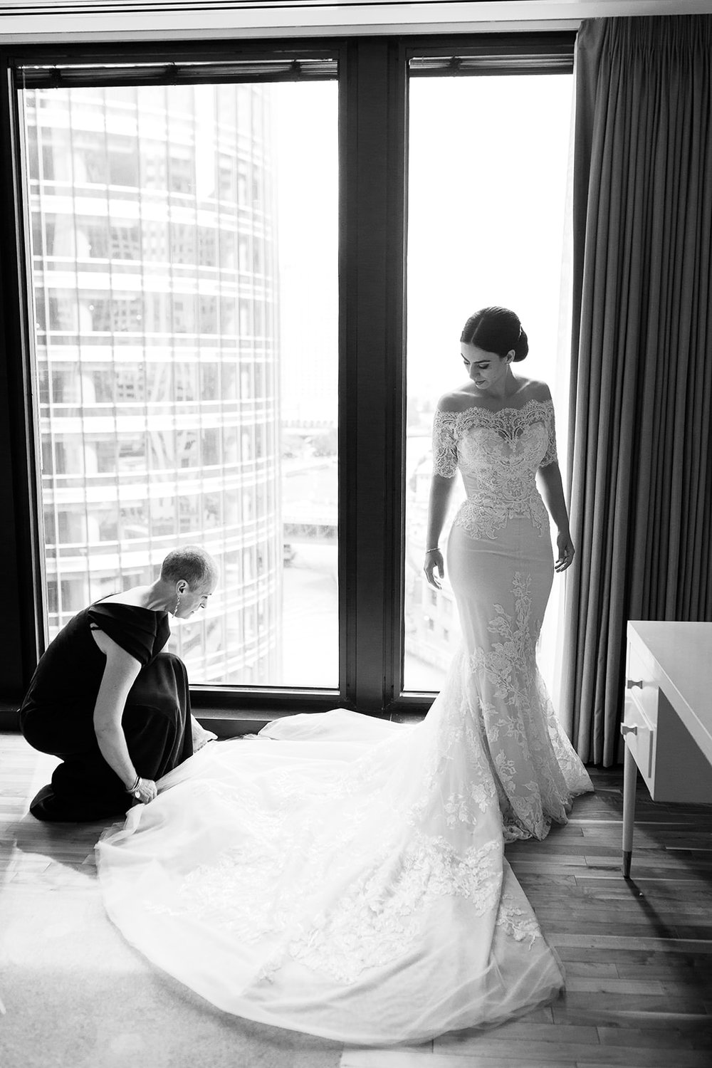 Mother of the bride helps her daughter into her wedding gown at the Langham in Chicago