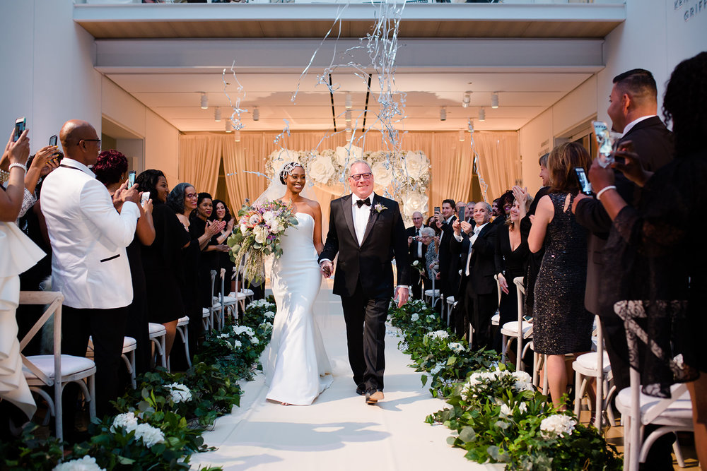 Modern museum wedding ceremony with streamers, confetti and giant flowers at the Art Institute of Chicago.