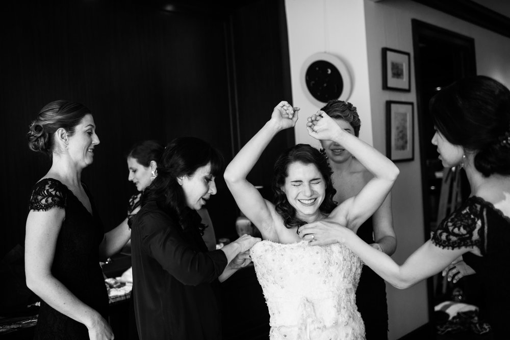 Our style of documentary wedding photography drives us to look for shots like this candid moment where Jenni's can't help but laugh as her mother and friends help her button her wedding dress.