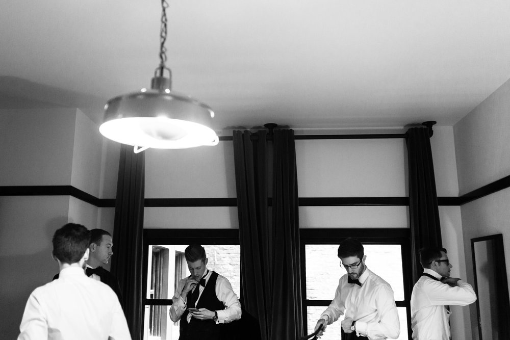 Love this symmetrical shot of the groom and his groomsmen watching videos about how to tie a bow tie at the Chicago Athletic Association.