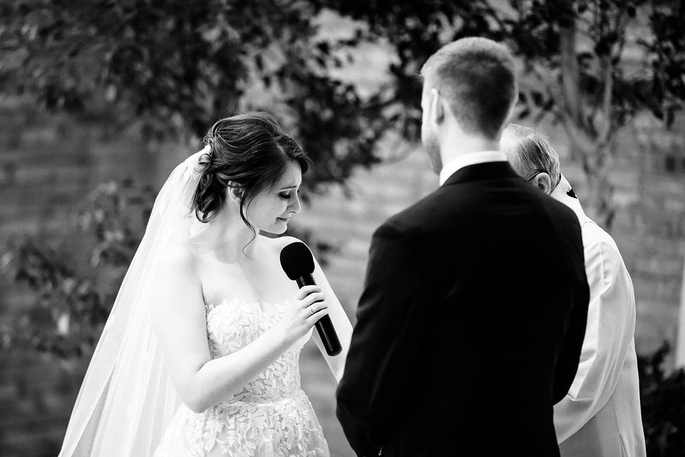 Emotional photography during the ceremony captures the feelings of the moments the bride and groom have been looking forward to years. This bride couldn't hold back tears as she read the vows she had written to her groom.