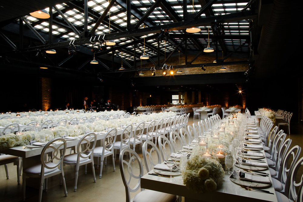 Does it get any better than this all white wedding reception dinner space? Long white dinner tables filled the room under the skylights provided by Revel Motor Row.