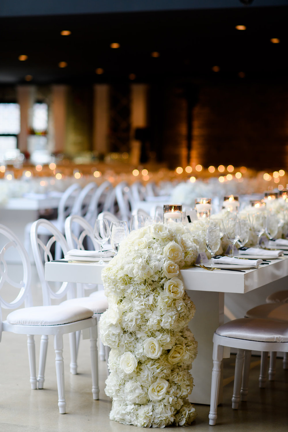 Cascading white roses and hydrangeas spilled over the tables.