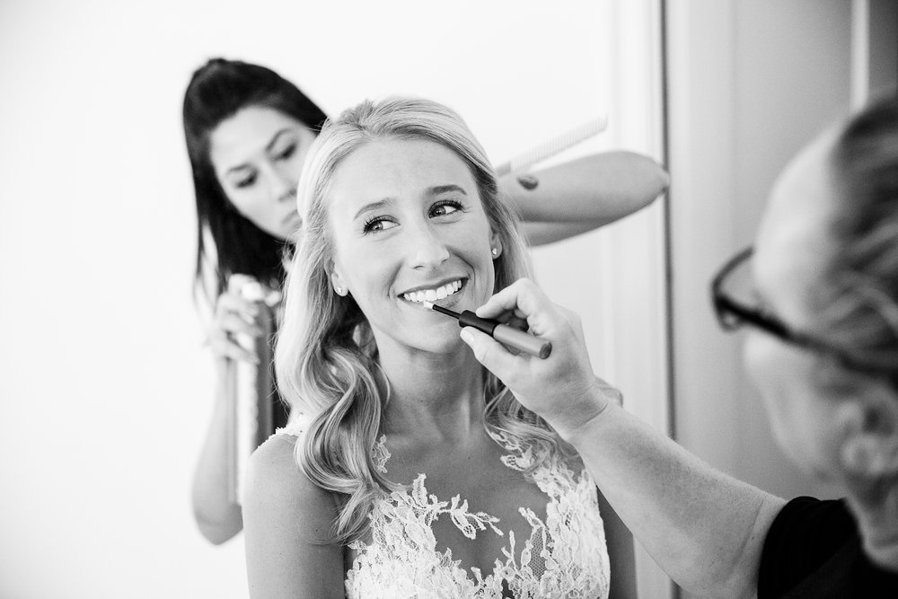 A bride dresses and has hair and makeup touches at the Ambassador Hotel in Chicago's Gold Coast neighborhood before her wedding at the Chicago History Museum.