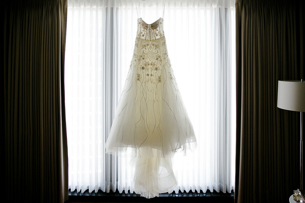 The bridal gown draped on the curtains of the Langham Hotel Chicago's bridal suite.