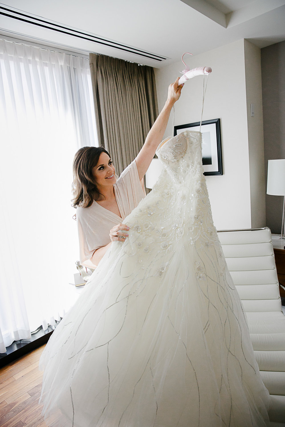 Sydney holds her designer bridal gown before dressing for her wedding at the Langham Hotel's bridal suite in Chicago.