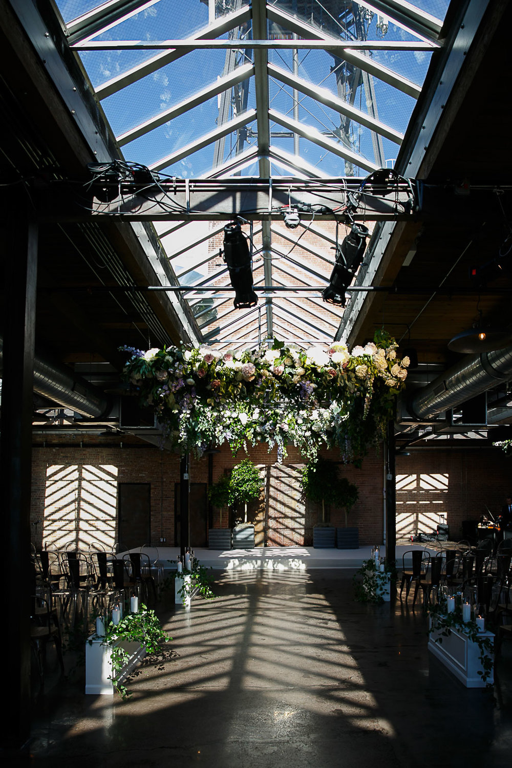 Hanging garden florals adorn the skylights down the aisle for a wedding ceremony at Morgan Manufacturing.